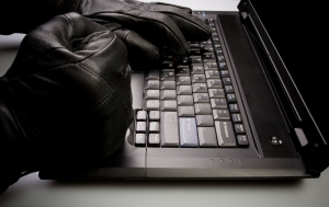 Security concept with mad hacker working on laptop at night